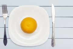 One whole orange on white plate. Fresh organic fruit. Healthy nutrition concept.  royalty free stock images