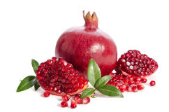 One whole and part of a pomegranate with pomegranate seeds Royalty Free Stock Image