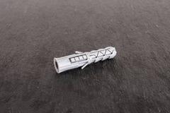 Work tool item on grey stone. One whole plastic light grey wall plug work item on grey stone royalty free stock photos
