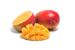 One whole ripe mango and a sliced half of a mango. Isolated on white background Stock Photography