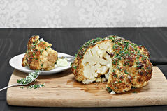 One whole roasted cauliflower head with a slice removed. Stock Images