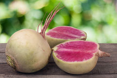 One whole and sliced watermelon radish on a wooden table with blurred garden background.  Stock Image