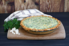 One whole spinach and feta cheese quiche on a cutting board. Stock Photo