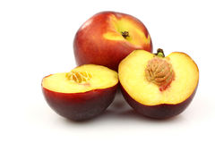 One whole and two nectarine halves Royalty Free Stock Images