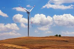 One windmill on the background of yellow grassland and blue sky. Montenegro, Niksic, wind power plant in Krnovo. One windmill on the background of yellow Royalty Free Stock Photo