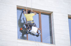 One window washer  hanging on rope Royalty Free Stock Photo