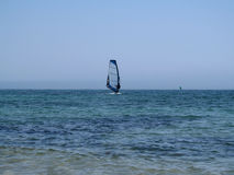 One windsurfer in the sea. Turquoise sea, clear blue sky without clouds and a surfer with a blue sail in the middle photo Stock Photos