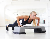 One woman doing abdominal push ups posture in gym Stock Photo