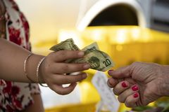 One woman hands another woman a twenty dollar bill against a blurred background. One woman hands another woman a twenty dollar bill against a blurred yellow royalty free stock photography