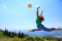 Female jumping in the air throwing her hat stock photography