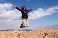 One woman jump for joy. Woman jumping for joy on top of the mountain over blue skies, freedom and happiness royalty free stock photography