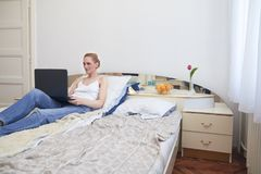 One woman, laying in bed smirking, using laptop. ordinary white room interior.  Stock Photo