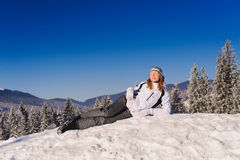 One woman lies on snow. Girl in winter clothes lies on ski slope in winter in mountains Stock Photo