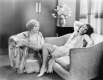 One woman massaging a friends leg Stock Images