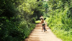 Parallax animation of a girl wearing a hat and sunglasses on a bicycle, looking over her shoulder. Taken in a dirt road in Sri Lan stock video