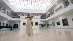 One woman plays violin alone, while standing in a room with paintings on walls. 4K stock video