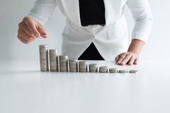 One woman putting coin on growth coins graph in white suit royalty free stock images