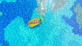 One woman rests in a blue pool, floating on a mattress. 4K stock footage