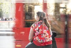 One woman sitting at a bus stop waiting Stock Image