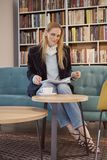 One woman sitting, 40 years old, holding magazine, book shop, book store, books on shelf behind out of focus.  Stock Photos