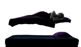Woman sleeping in levitation on bed silhouette stock photography