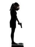 Woman standing on weight scale  despair aiming gun silhouette Royalty Free Stock Photo