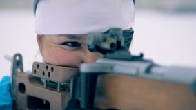 One woman stands and aims with a sports rifle, while competing. 4K stock footage