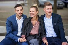 One woman and two men sitting on bench togehter. One women and two men in suits sitting on bench togehter Royalty Free Stock Photo