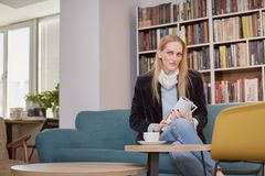 One woman, 40 years old, holding magazine, sitting in book store, book shop, library, shelf full with books behind out of focus.  Stock Photos