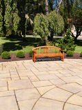 One wood bench. One empty wood bench by a stone patio royalty free stock photography