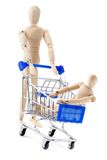 One wooden dummy rolls another in shopping cart. Royalty Free Stock Image