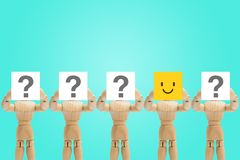 One wooden figure holding face emotion in happiness and other figures holding question mark in hand. One wooden figure mannequin holding face emotion in royalty free stock photo