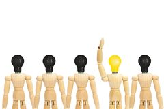 One wooden figure mannequin with yellow light bulb head standing out row of other figures with black light bulb on head. Business Idea Concept : One wooden royalty free stock images