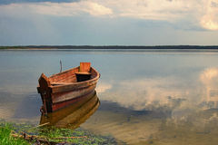 One wooden fishing boat on bank of the lake. Spring landscape photo. Volyn region. Ukraine Stock Image