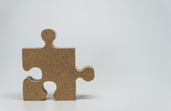One Wooden piece of jigsaw puzzle with white background and selective focus Stock Image