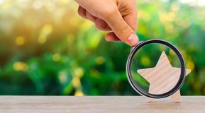 One wooden star. Rating hotel, restaurant, hotel. Overview. appreciation of the critic. Negative feedback. poor quality. Of service. green bokeh background stock photo
