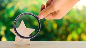 One wooden star. Rating hotel, restaurant, hotel. Overview. appreciation of the critic. Negative feedback. poor quality. Of service. green bokeh background stock photos