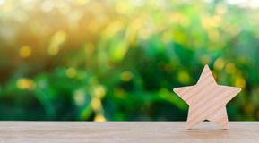 One wooden star. Rating hotel, restaurant, hotel. Overview. appreciation of the critic. Negative feedback. poor quality of service. Green bokeh background royalty free stock image