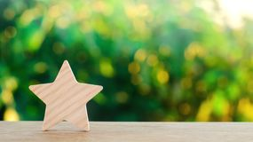 One wooden star. Rating hotel, restaurant, hotel. Overview. appreciation of the critic. Negative feedback. poor quality of service. Green bokeh background stock photo