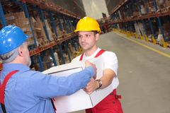 One worker receiving box from another. In warehouse stock photography