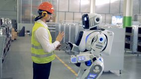 A man talks to robot at a factory. One worker says to a robot what to do