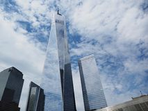One World Trade Center on cloudy sunny day with glass reflection royalty free stock images