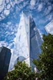 One World Trade Center die gewikkeld en op witte pluizige wolken in de blauwe hemel wijzen stock foto