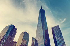 One World Trade Center on the New York skyline. Showing the modern design and glass facade in a low angle perspective against a toned cloudy blue sky Royalty Free Stock Photography