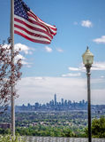 One WTC and the US Flag. View on lower Manhattan with the finished One World Trade Center (One WTC) skyscraper and an US flag in the foreground, as seen from Stock Image