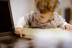 Baby clicks on laptop keys. The one-year baby clicks on laptop keys royalty free stock image