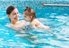 One year baby girl at her first swimming lesson with mother Stock Photos