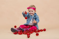 One year baby portrait. Portrait of young cute baby on beige background with christmas balls Royalty Free Stock Photography