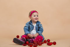 One year baby portrait. Portrait of young cute baby on beige background with christmas balls Royalty Free Stock Images