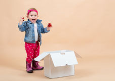 One year baby portrait. Portrait of young cute baby on beige background with white paper box Stock Photography